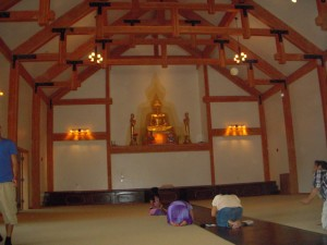 The interior of the meditation hall features a high ceiling supported by large wooden beams, and a large gold Buddha