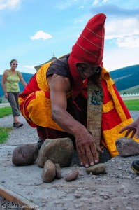 Tulku Sang-ngag places stones under the suppression stupa, to hold negativity at bay