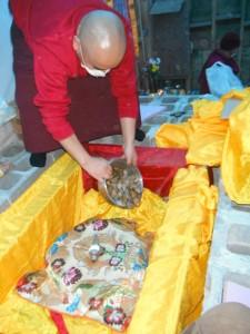 Tulku Karzang filling concrete pedestal