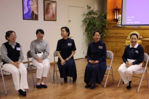Commissioners Hsiang Fong, and Su Wei (in blue uniforms) of the Tzu Chi Foundation lead a discussion-and-sharing session with new volunteers, beneath a picture of Buddhist Master Cheng Yen, founder of Tzu Chi.