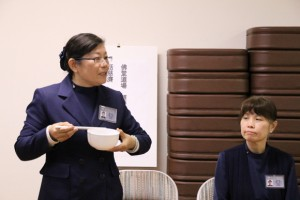 Tzu Chi Commissioner Wen Shing Hua explains how to properly hold rice bowl and chopsticks, as part of training Tzu Chi volunteers to act with composure, dignity, and elegant manners