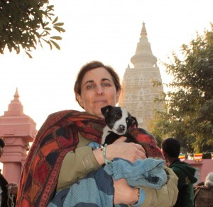Eileen Weintraub holds Shyam, a rescued puppy, in front of Mahabodhi Stupa in Bodhgaya, India. Shyam shortly afterward died of distemper at a shelter, which motivates us to improve standards there.
