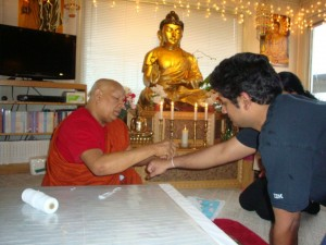 Bhante Polwatte Pagnananda ties a blessing cord on a man at the center.