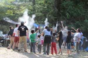 Tibetan parents and children, from the Tibetan Language & Culture Class, throw tsampa in the air to invoke a safe and pleasant experience during their annual camping trip to Moran State Park on Orcas Island, Wash. Tsampa, roasted barley flour, is a traditional Tibetan food.