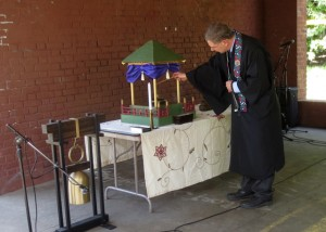 Rev. Gregory Gibbs, from the Oregon Buddhist Temple, lights a stick of incense from an altar.