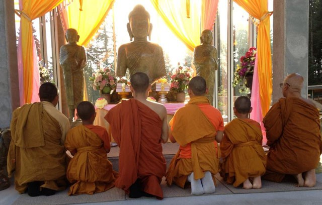 Monks gather around the Buddha statues