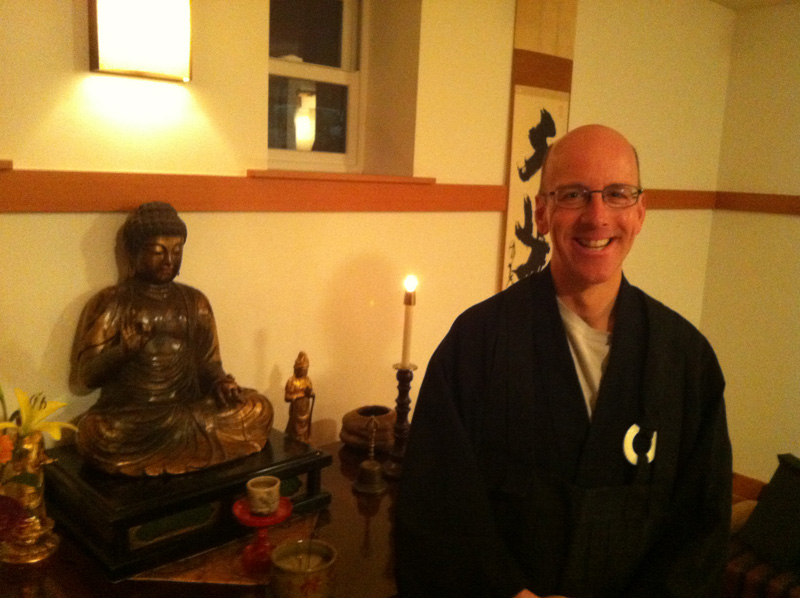 """Peter Ilgenfritz at the Cho Bo Ji altar, wearing his rohatsu around his neck. His dharma name there, which he received when he became a member, is Shinke, which means """"Profound Home"""""""