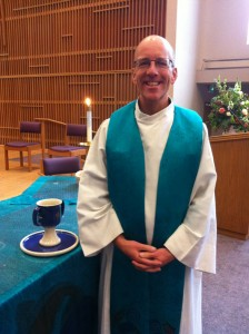 Ilgenfritz by the communion table at University Church, dressed in the white robe he wears each Sunday. The green stole indicated he is ordained pastor