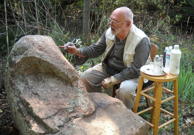 Sanje Elliott, who paints Tibetan sacred art, creates an image on a boulder