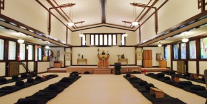 Inside the zendo, zabutons and zafus are arranged in rows, with meditators facing the walls