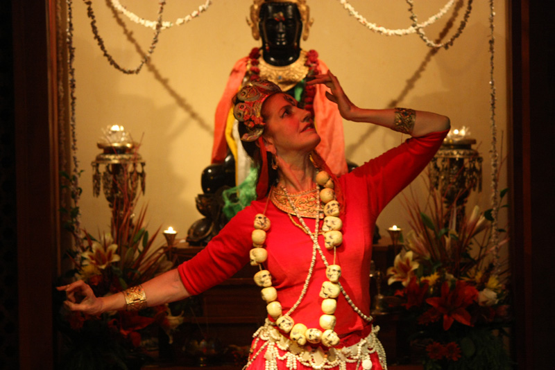 Helen Appel appears in dance as Vajrayogini in all her red glory, holding a vajrachopper in her right to actively cut through tight self-clinging.