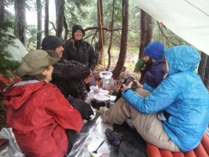 The group warms their toes around a hot pot of water near Obsidian Falls.  From left to right: Lesli Dalaba, Bob Penny, Georgia Mitchell, Sergey Feldman, Emily Buck.