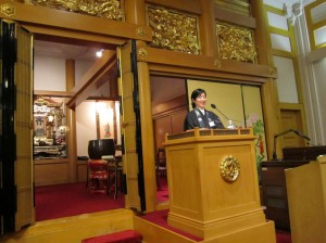 Rev. Mariko Nishiyama speaking, from inside the main shrine room at the temple