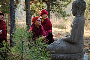 Khenpo Lodro Donyo Rinpoche with basalt Buddha statue near the cloisters. Lama Michael Conklin and Lama Tashi Dondrup behind