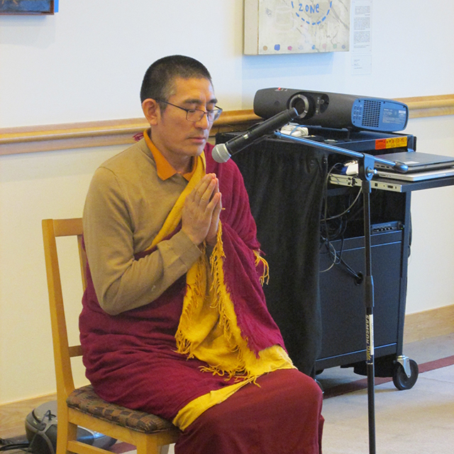 Ven. Tulku Yeshe Gyatso praying, before sharing his songs of Tibet