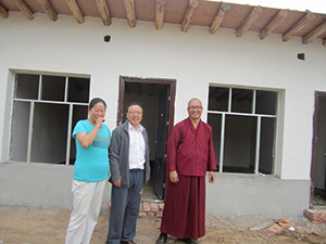 Dr Tsering Kyi, Dr Lasumgya (dean of School of Tibetan Medicine at Qinghai University); and Kunchok Gyaltsen, in front of the building site for the additional 14 rooms