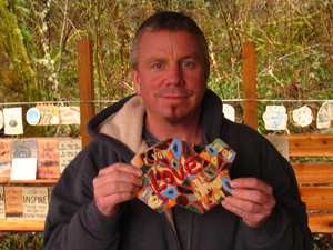 A participant of the week-long retreat on life vows, shows his hand-made tile to be placed at the Shrine of Vows
