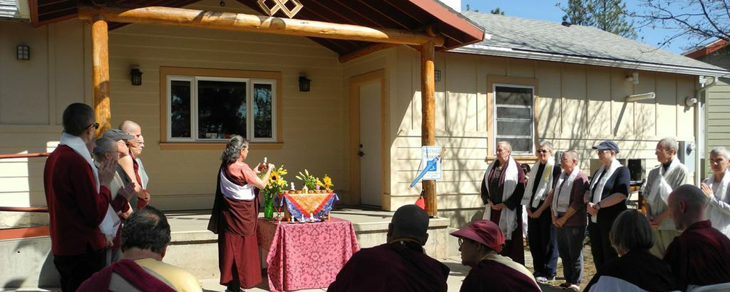 Lama Donna Albino making offering during rituals before one-year retreat. Retreatants to each side and kitchen beyond