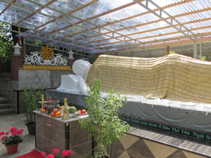 Under a protective roof, but almost outdoors, the 26-foot reclining Buddha radiates serenity.