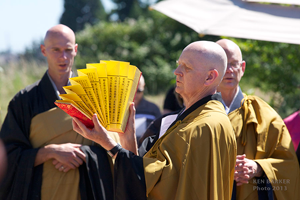 Kyogen Carlson, co-abbot of Dharma Rain Zen Center, fanning the surtras at the ground-breaking blessing ceremony. Behind are Kakumyo Lowe-Charde, DRZC resident priest and project manager, and Hogen Bays, co-abbot of Great Vow Zen Monastery