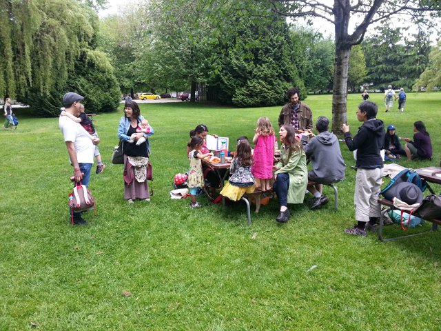 The children and their parents gather for a picnic in a Vancouver, B.C., park