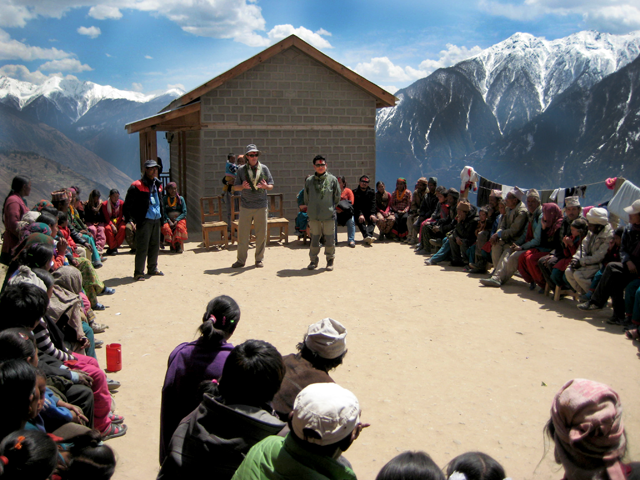 Namaste Children's Fund General Manager Chimey Sherpa (standing on right), Phil Crean (middle) and school Administrator Suresh Bohara (standing on left) lead a discussion with parents in the school courtyard