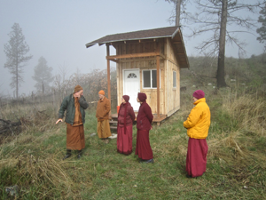 Tan Khemako (left) and Ajahn Jotipalo show the nuns a kuti—a meditation hut—on their retreat property. From left to right the nuns are Ven. Chonyi, Ven. Damcho, and Ven. Samten