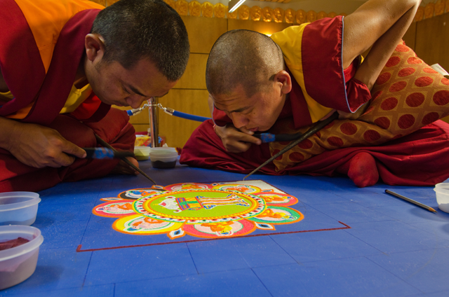 With intense concentration, two monks create a Medicine Buddha sand mandala at Maitripa College