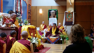 """Yangsi Rinpoche smiles as students begin to sing """"Happy Birthday"""" and a huge cake with candles is brought into the room, as Lama Zopa Rinpoche smiles, too"""