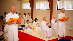 "Ordinants Chayanon ""Mac"" Sontidpanya and Baumgartner take their vows in the Seattle Meditation Center as congregants watch"