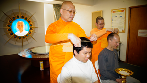 Venerable Manikanto Bhikkhu (abbot of the Seattle Meditation Center), cuts Sontidpanya's hair, while Venerable Pormov Bhikkhu (instructor of novices), cuts Baumgartner's hair
