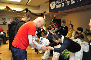 Tzu Chi volunteers offer relief aid, with a deep bow to show love and respect, to homeless people at a Salvation Army Shelter. Winter coats and daily necessities are among the items offered