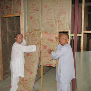 Ven. Trung and a fellow monk install insulation in the new temple this summer