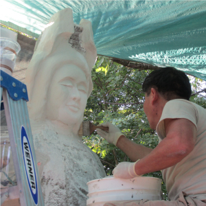 A sculptor and temple supporter works on the Kuan Yin statue