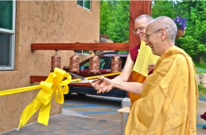 Abbess Ven. Thubten Chodron and Construction Manager Ven. Thubten Tarpa cut the ribbon together