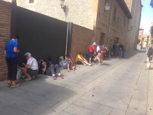 Tired pilgrims wait for an albergue to open