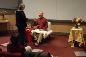 Anam Thubten (seated) discusses the dharma with Susan Dixon (standing)