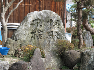 "A stone, outside the home temple of Shin Buddhist priest and human rights activist, Asano Onchi, with with the phrase ""grasped, never to be abandoned."" This refers to the way that the ordinary being will not be rejected by Amida's compassion."