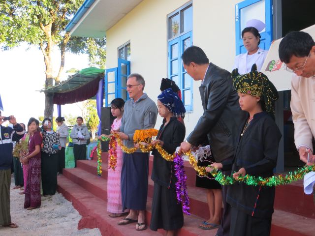 Steve Armstrong and the minister of education and health in Shan State, Myanmar, cutting the ribbon at the grand opening ceremony of Rural Health Center in Bimie, Myanmar. This was funded by Rich and Sharon Stewart of Mt. Vernon, Wash.