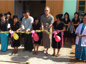 A rural doctor, village girls dressed in ethnic clothing, the Shan State Senator, and Steve Armstrong, cutting the grand opening ribbon at a mid-wives' clinic in Chaung Ni Poke, Myanmar. This was funded by Claude Ginsburg and Lynne Hyerle of Ballard, Wash.