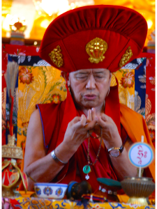 H. E. Garchen Rinpoche offering a mandala and wearing the Red Hat of the Drikung Kagyu lineage.