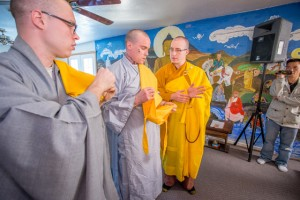 Master of ceremonies, Sunyananda Dharma, helps Richards on with his new robes called kesas. Novice Thich Tam Bi is to the left