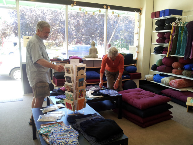 Two customers look over cushions and other goods at the store