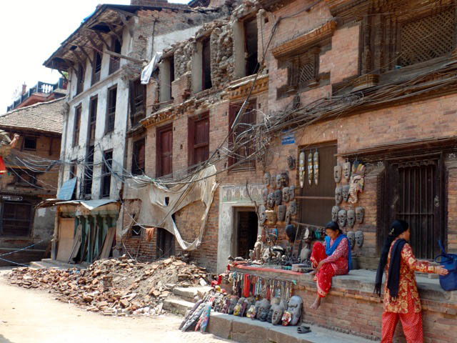 A woman has re-opened her shop outside in Bhaktapur, in the Kathmandu Valley, even though the building behind her looks like it's going to sink.