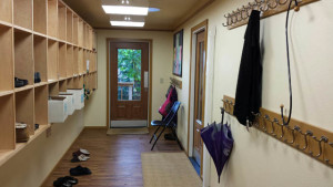 The completed mudroom (facing east). Personal cubbies on left, coat hooks on right, energy-efficient lighting above, dry floor below