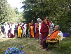 Sangha members present traditional khata offering scarves to His Holiness the Fourth Dodrupchen Rinpoche during his 2014 visit to Whidbey Island
