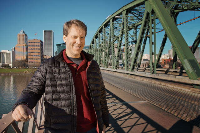Author Paul Louis Metzger, standing on a bridge in Portland