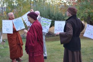 Venerable Thubten Chodron (left), abbot of of Sravasti Abbey, helps hang prayers flags to bless Sravasti Abbey's land