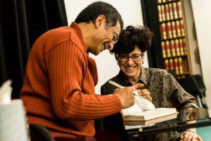 Karen de Luna, co-coordinator of the weekend teaching, laughs as Ponlop Rinpoche signs a book for her husband, Cadin Batrack