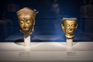 Two gilded bronze Buddha heads, one from Thailand and the other from Nepal, from the 17<sup>th</sup> century.